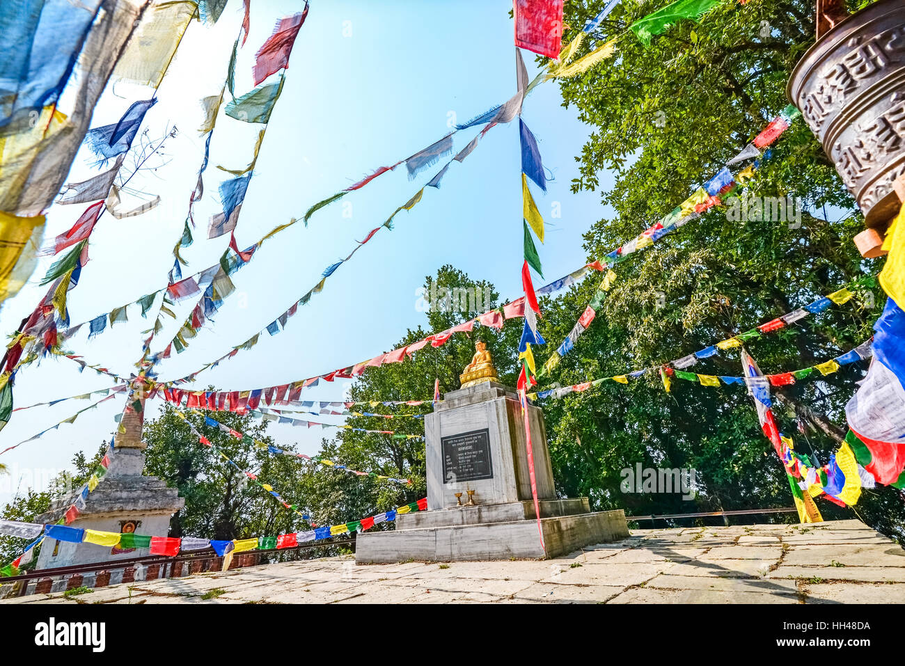 Golden Buddha statue surrounded by Nepali prayer flags atop Panchase Peak, Kaski, Nepal. © Reynold Sumayku - Stock Image