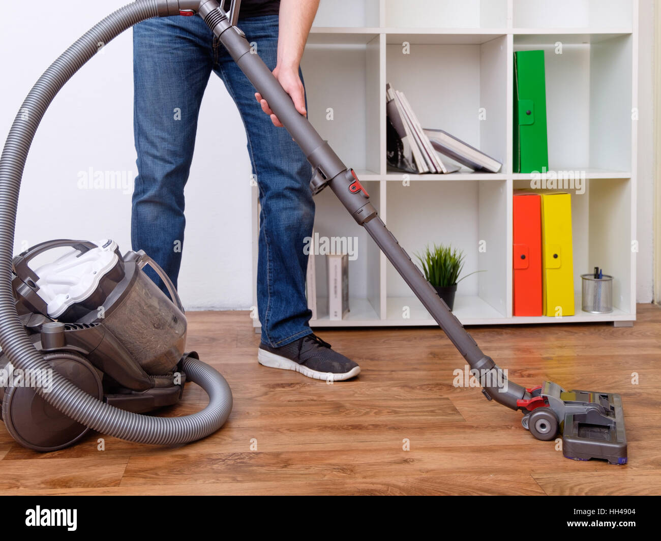 Hoovering a parquet floor - Stock Image
