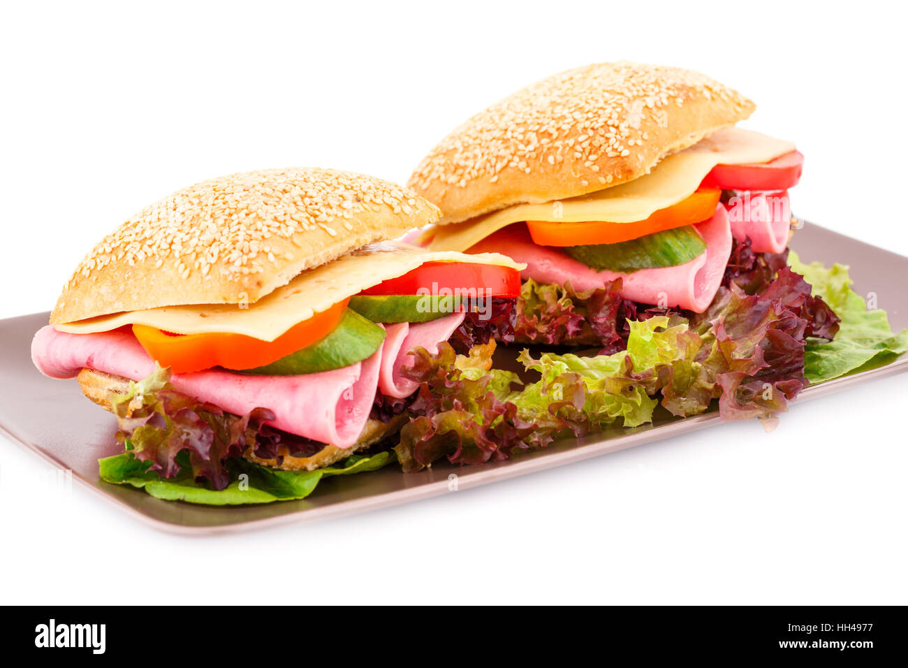 Sandwiches with fresh vegetables, ham and cheese on plate. - Stock Image