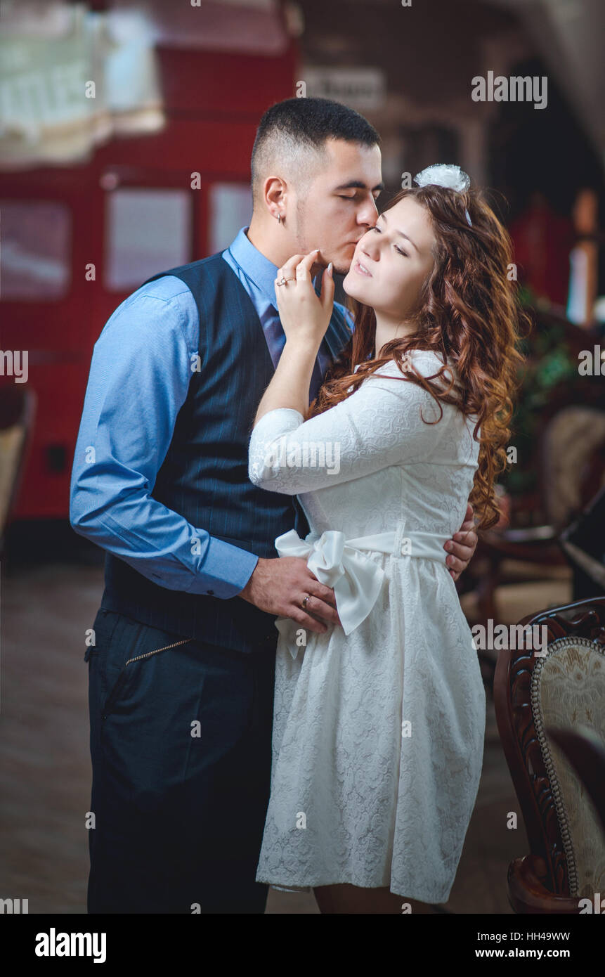 The young loving couple embraces and kisses. The girl in a white ...