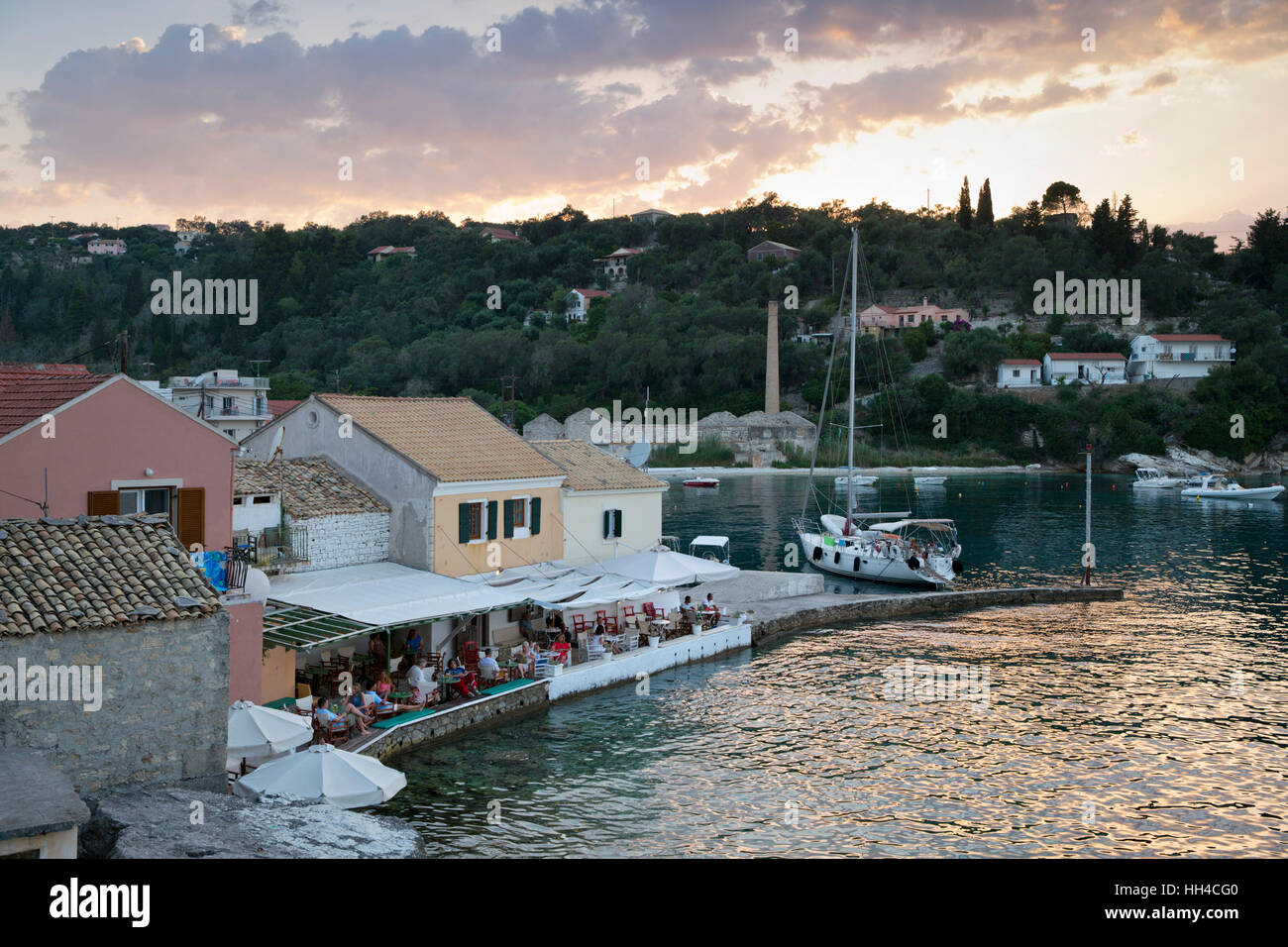 View over harbour and waterfront bars at sunset, Loggos, Paxos, Ionian Islands, Greek Islands, Greece, Europe - Stock Image