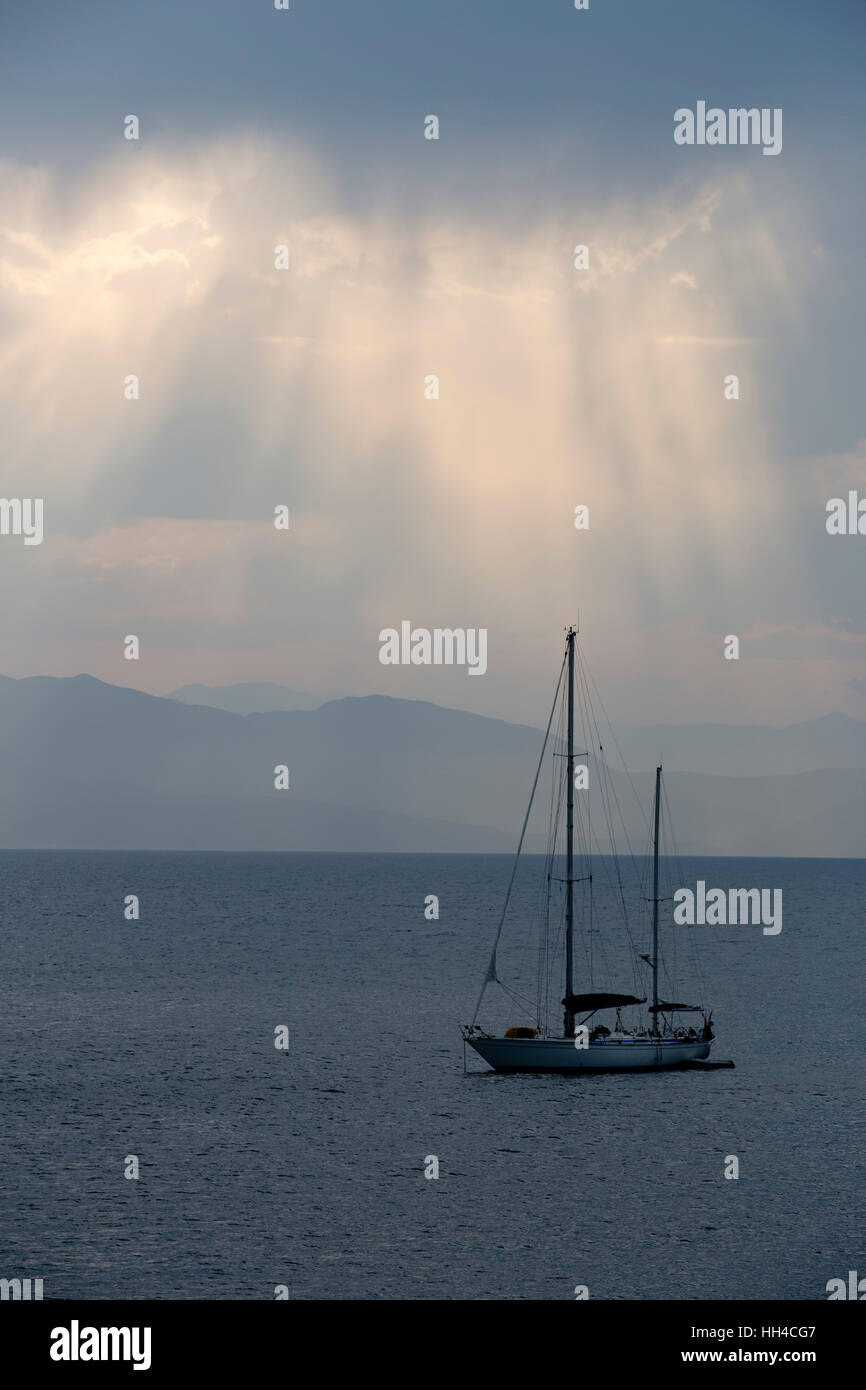 Yacht and sun beams, Loggos, Paxos, Ionian Islands, Greek Islands, Greece, Europe - Stock Image