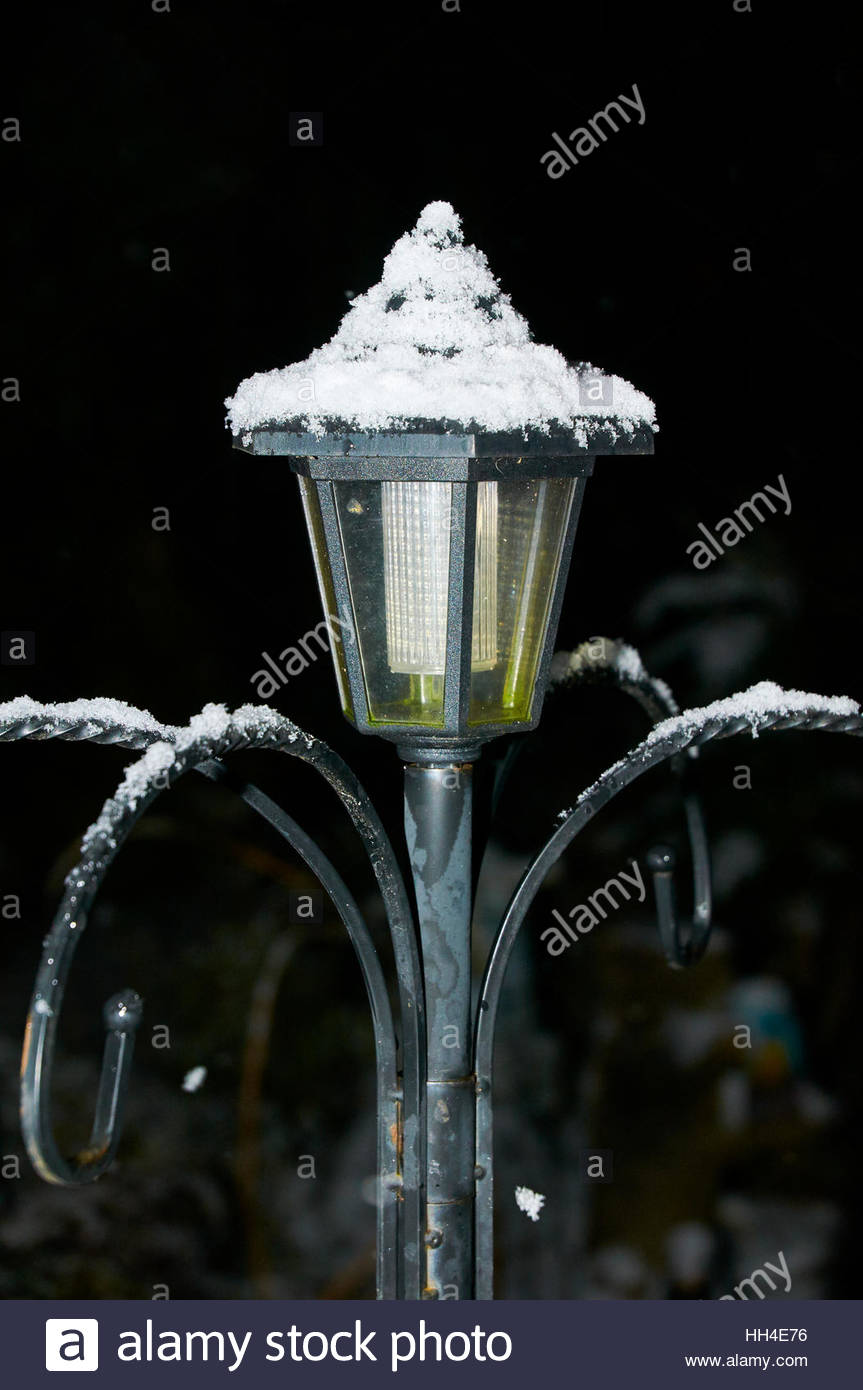 Ornamental garden light not lit covered in snow in the wintertime during nightime - Stock Image