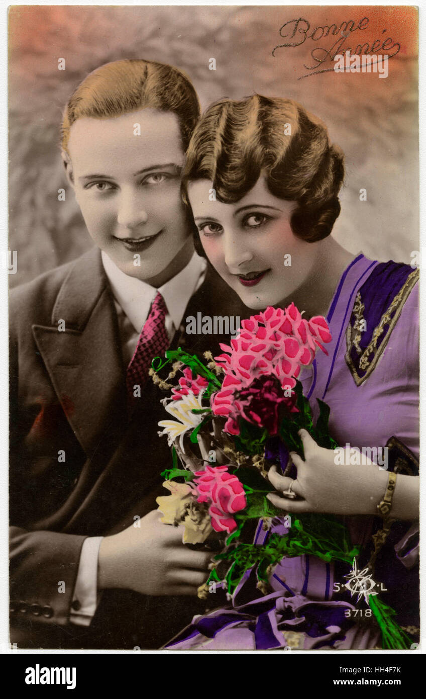 kitsch new years greetings postcard featuring a young couple stock image