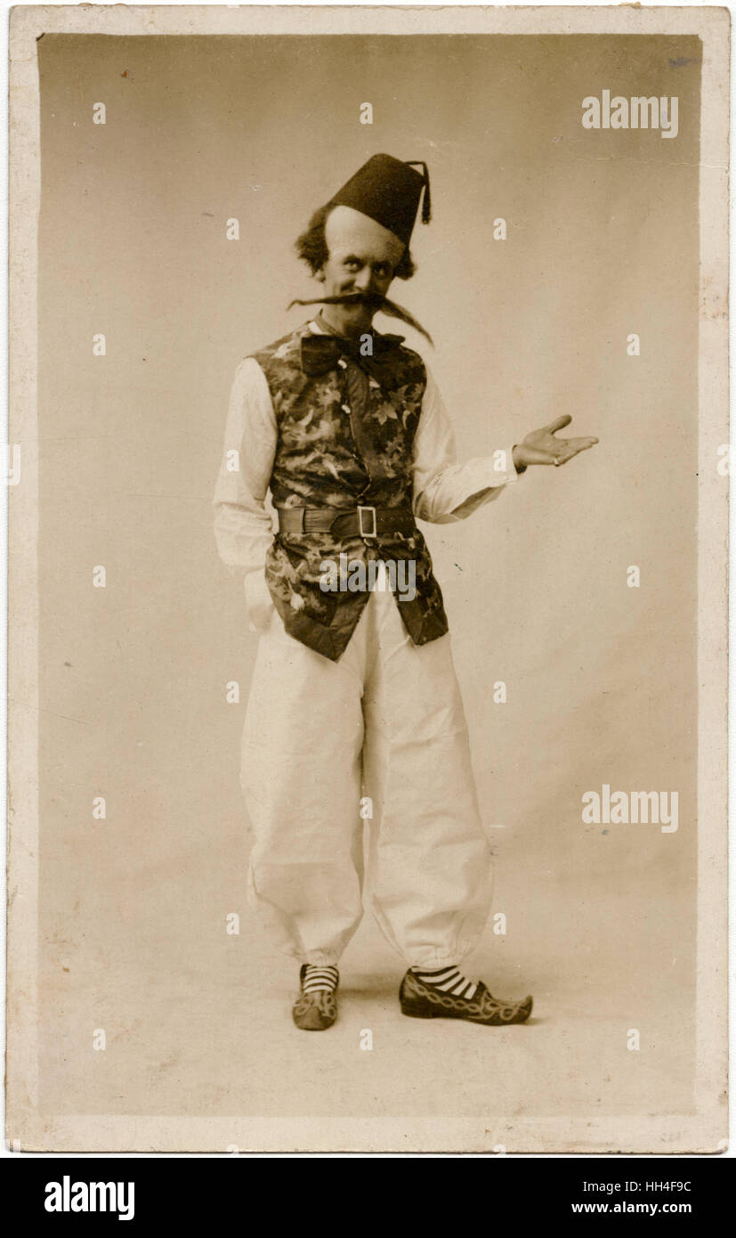 English comic stage performer (or clown?) wearing Arab Clogs, a fez a massive moustache, fake enlarged head and - Stock Image