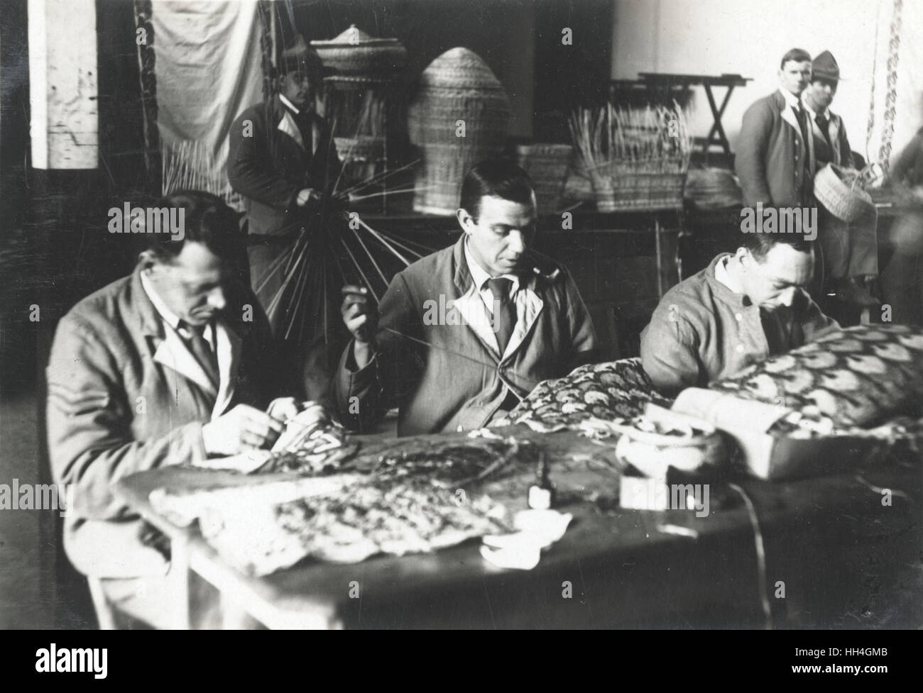 Wounded First World War soldiers wearing Hospital Blues, making baskets and sewing basket linings in the workshops - Stock Image