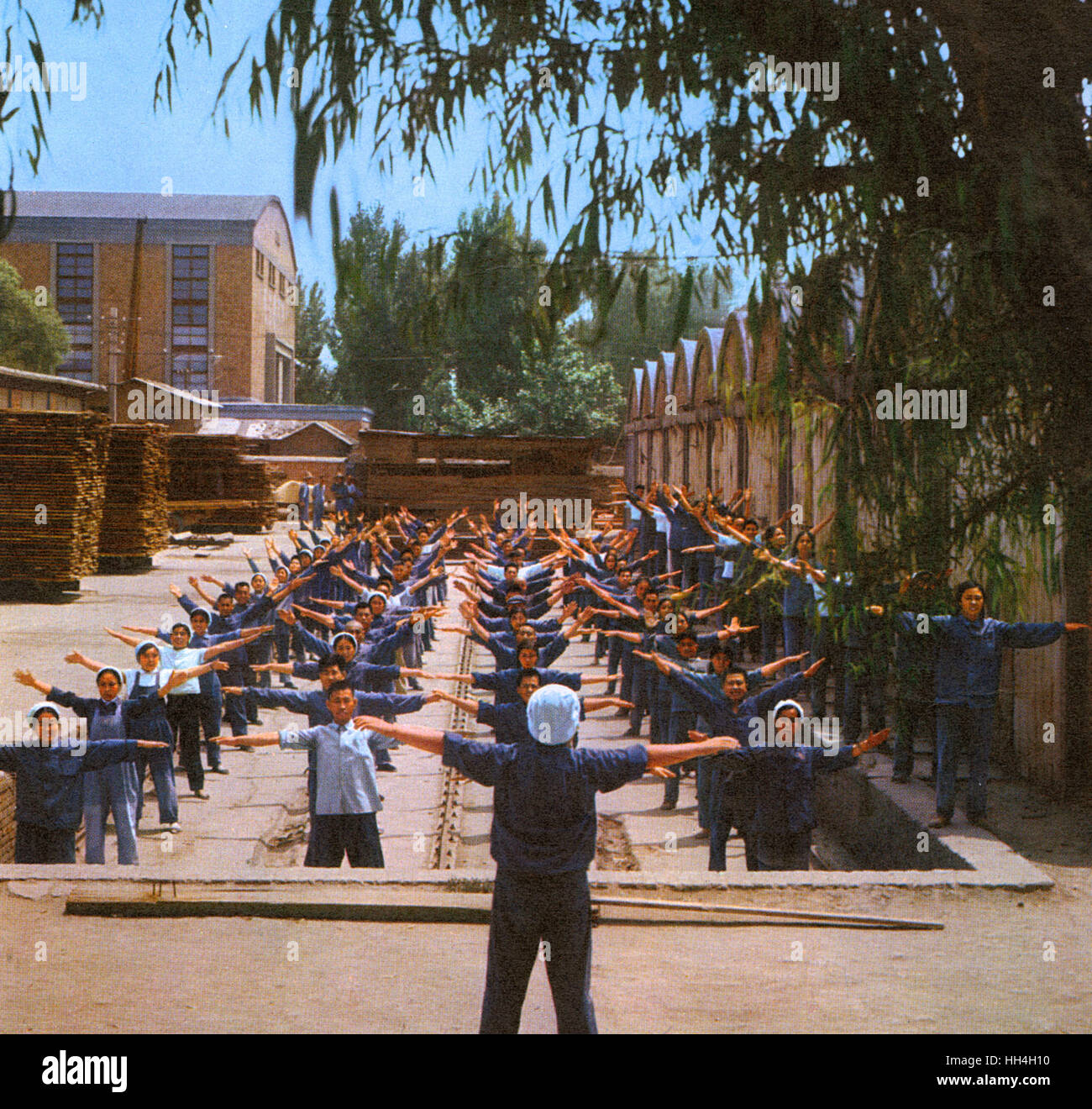 Communal exercise session for timberyard workers during the Cultural Revolution era in Communist China. - Stock Image