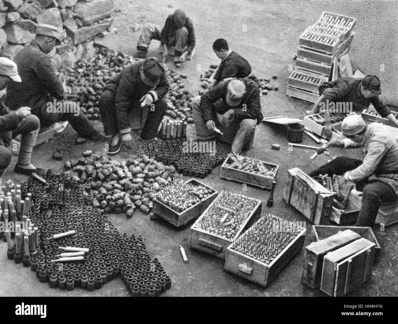 Communist China - soldiers sorting weapons and boxes of ammunition captured from the enemy, probably during the - Stock Image