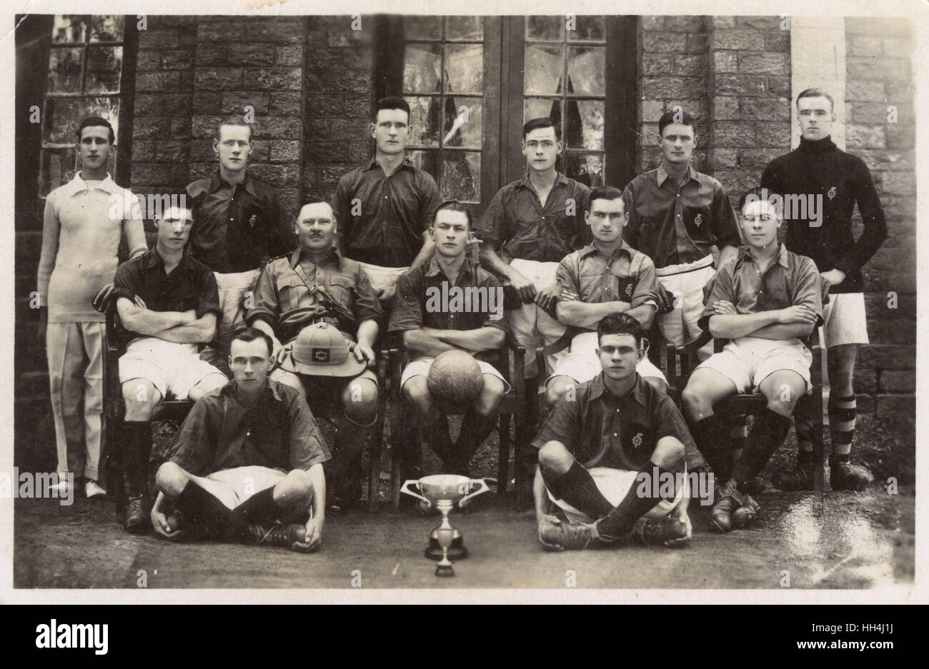 Group photo, Royal Sussex Regiment football team with ball and two trophies (unknown location). - Stock Image