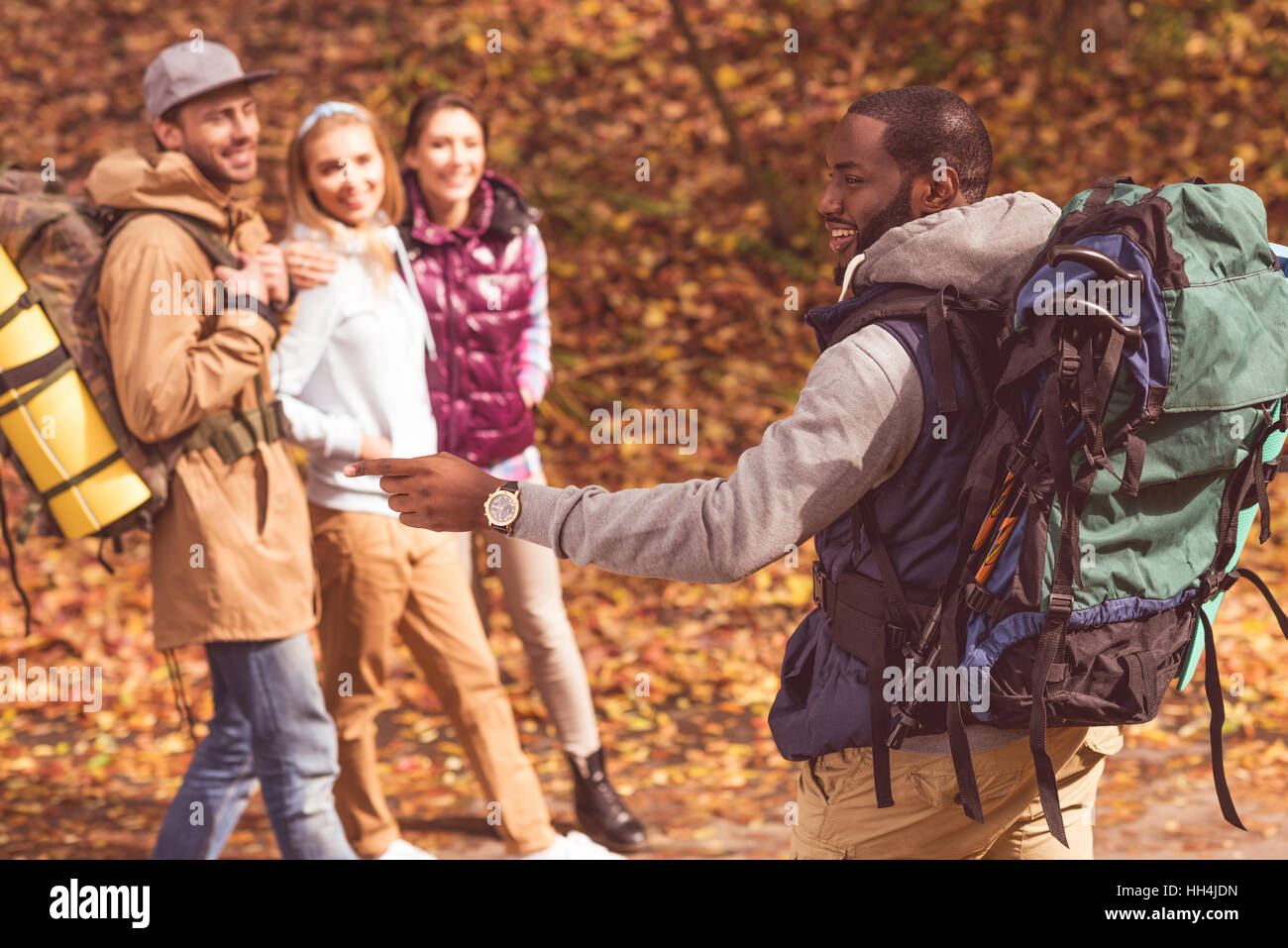 Young smiling african man pointing with finger and talking with friends in autumn forest - Stock Image