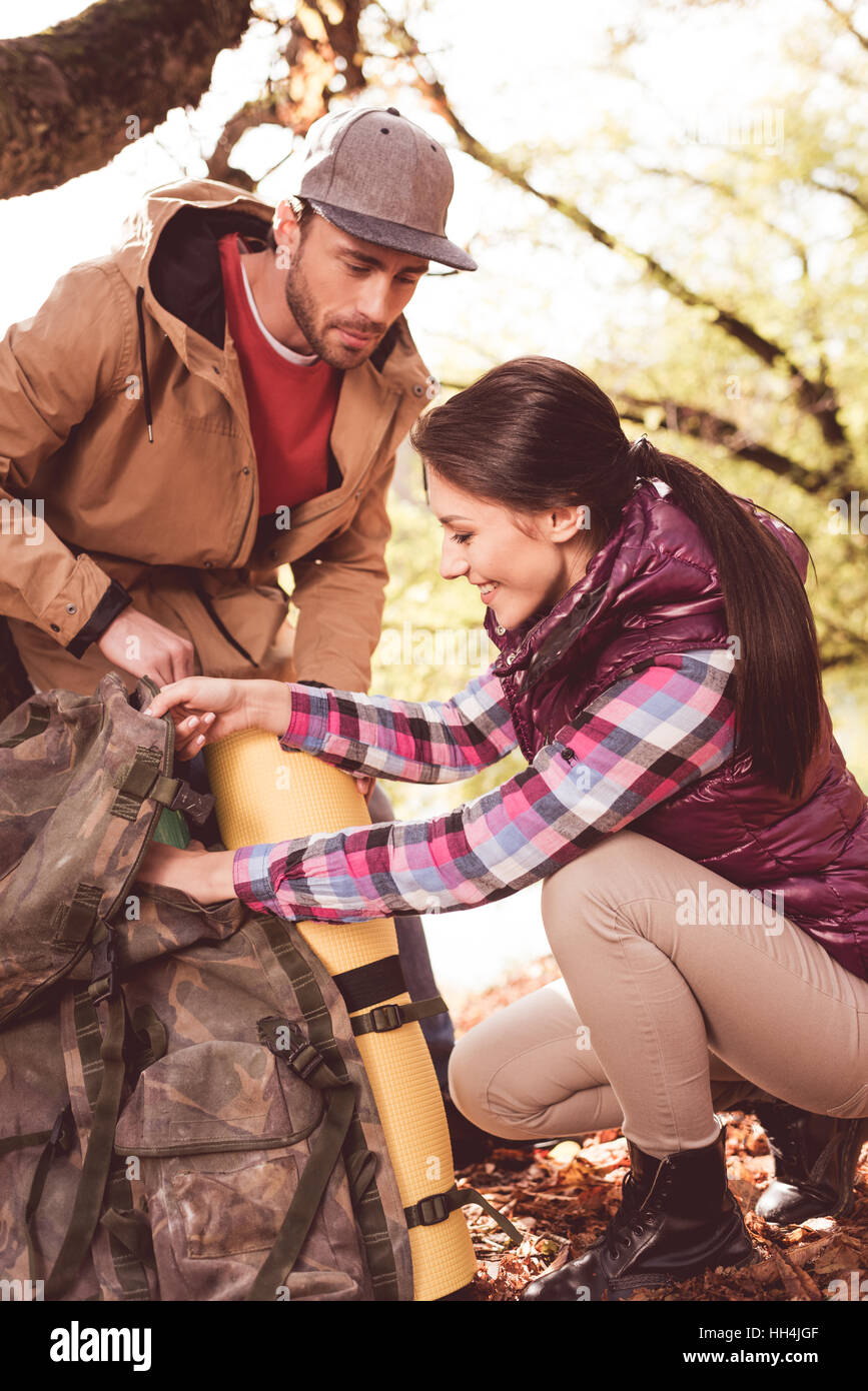 Young man looking at beautiful woman packing backpack in autumn forest - Stock Image
