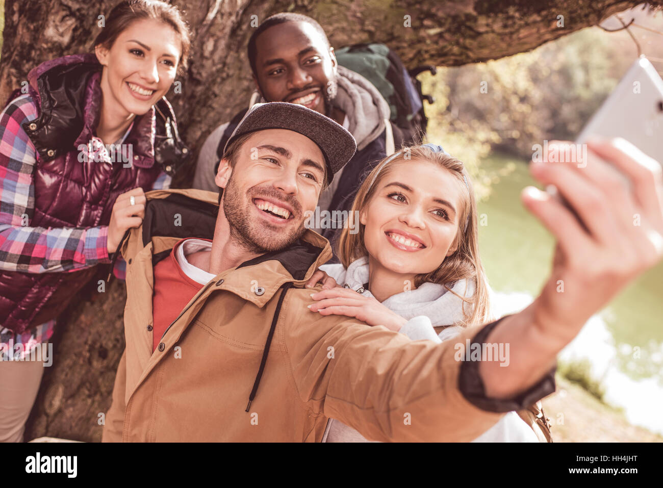 Group of young people standing near huge tree and taking selfie near calm forest river - Stock Image