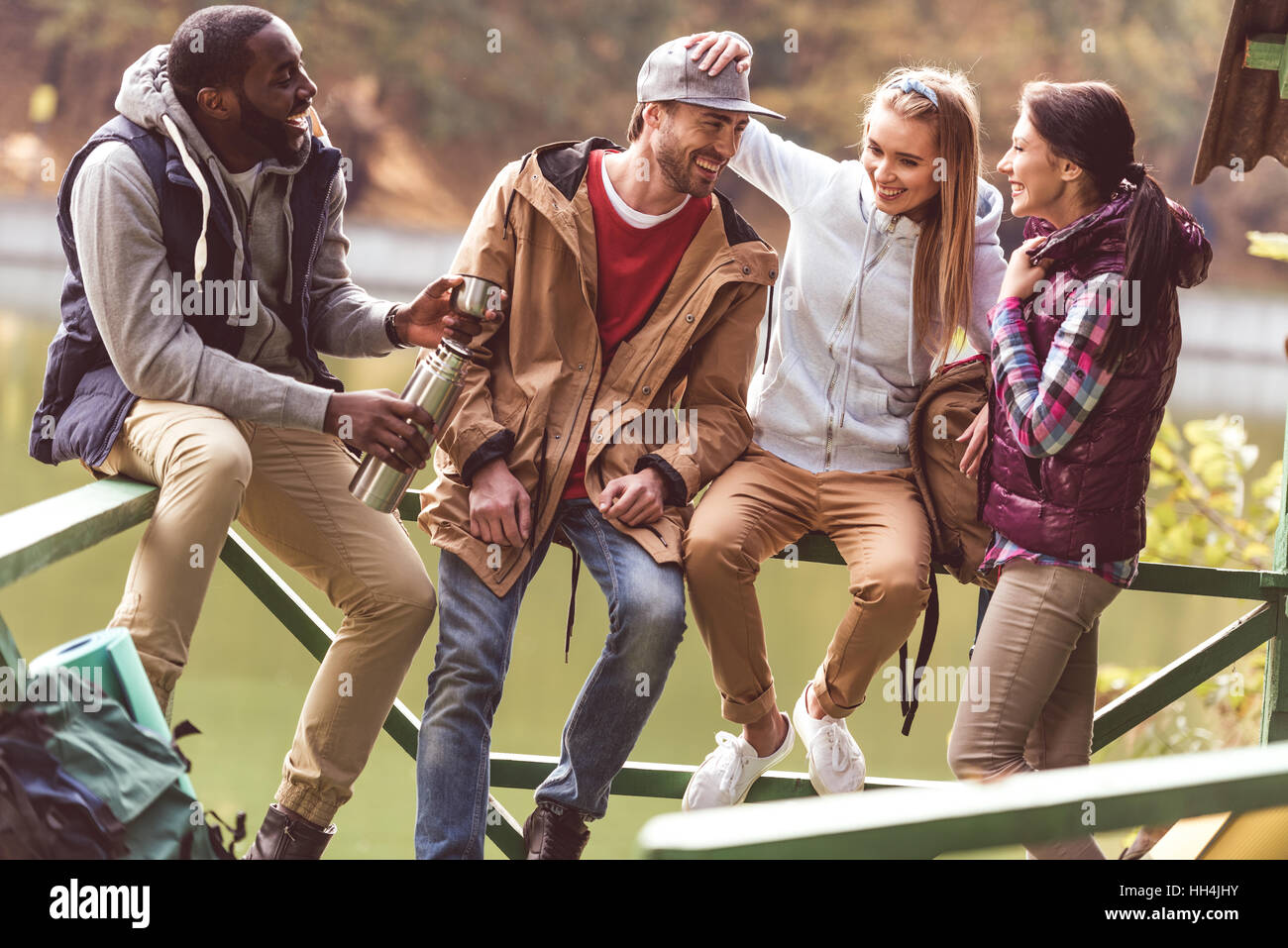 Group of young friends travelers resting near calm river in autumn forest - Stock Image