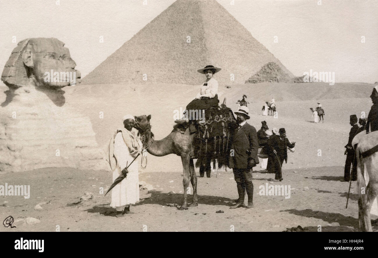 Tourist woman riding a camel accompanied by a man and a local guide in Giza, Egypt. In the background the Great - Stock Image