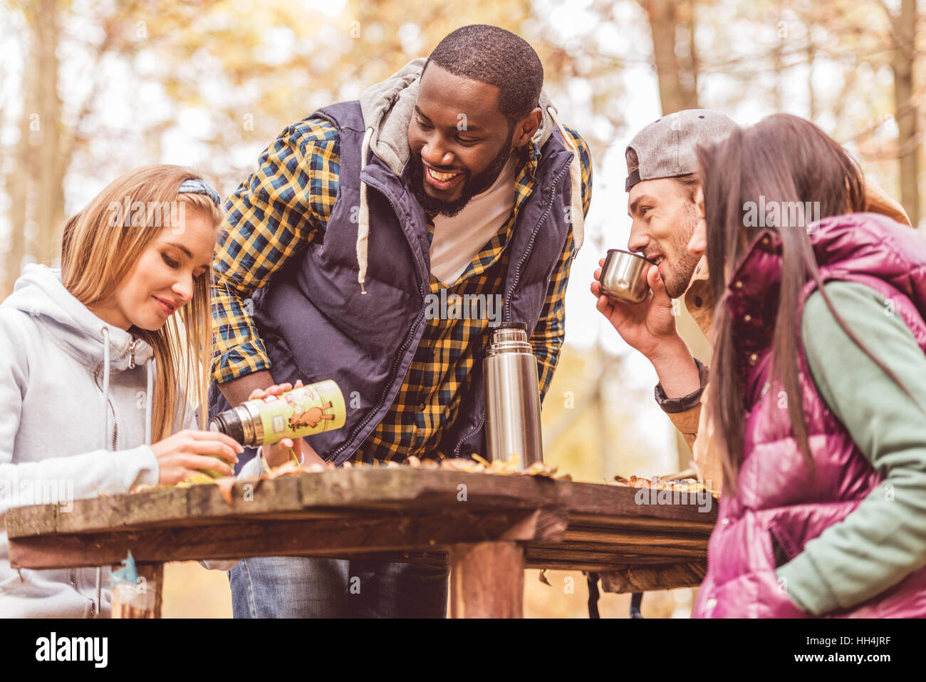Group of smiling friends sitting at wooden table and pouring hot drink in autumn forest - Stock Image
