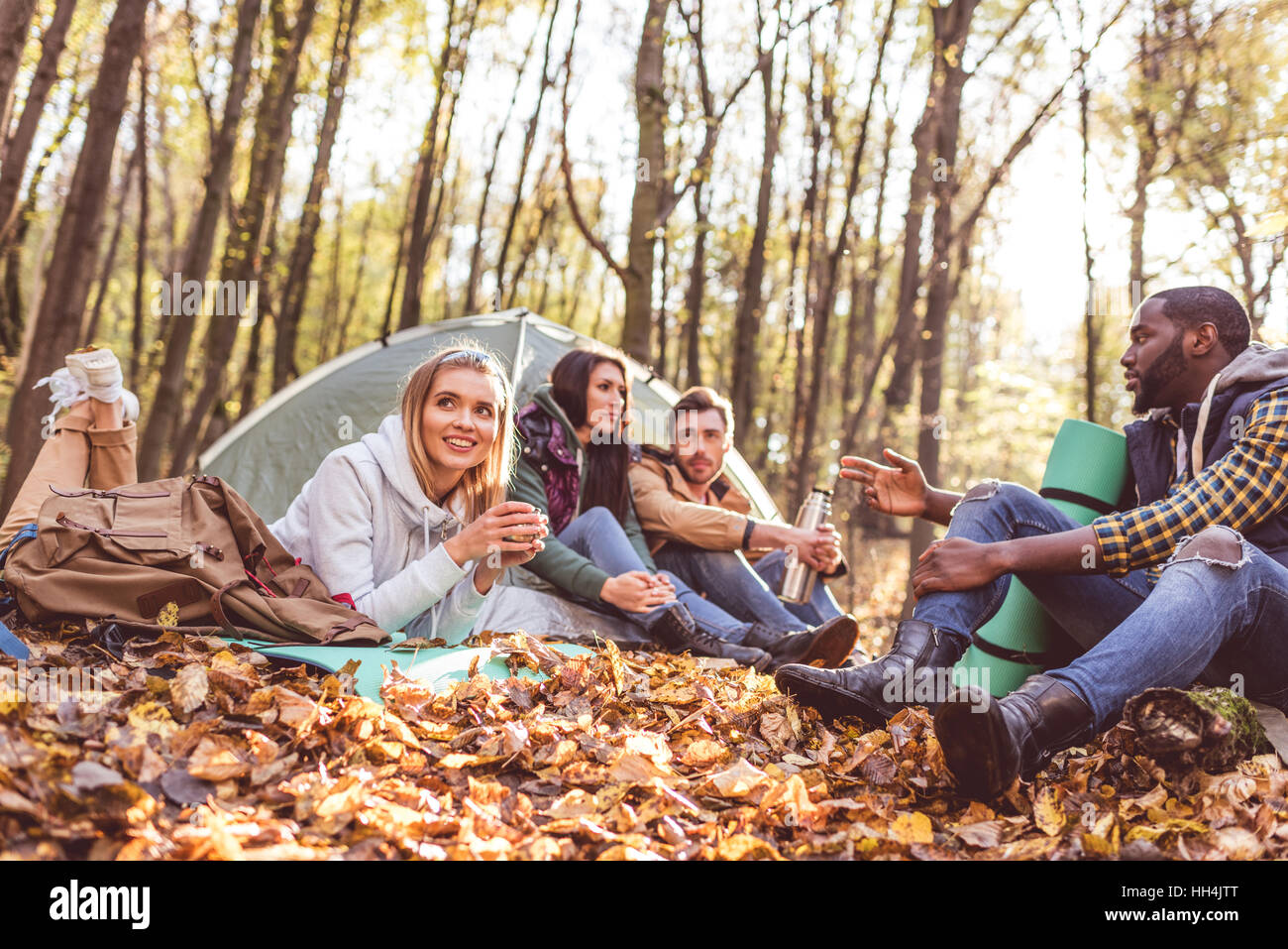 Young friends travelers sitting and talking near tent in autumn forest - Stock Image
