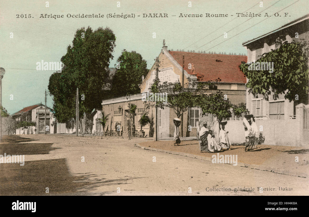 A. O. F. (Afrique occidentale française) Theatre at Avenue Roume with women carrying bowls and baskets on their - Stock Image