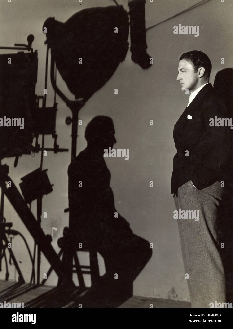 Clive Brook specially poses for the cameraman during the filming of 'The Man From Yesterday' (1932) - Promo - Stock Image