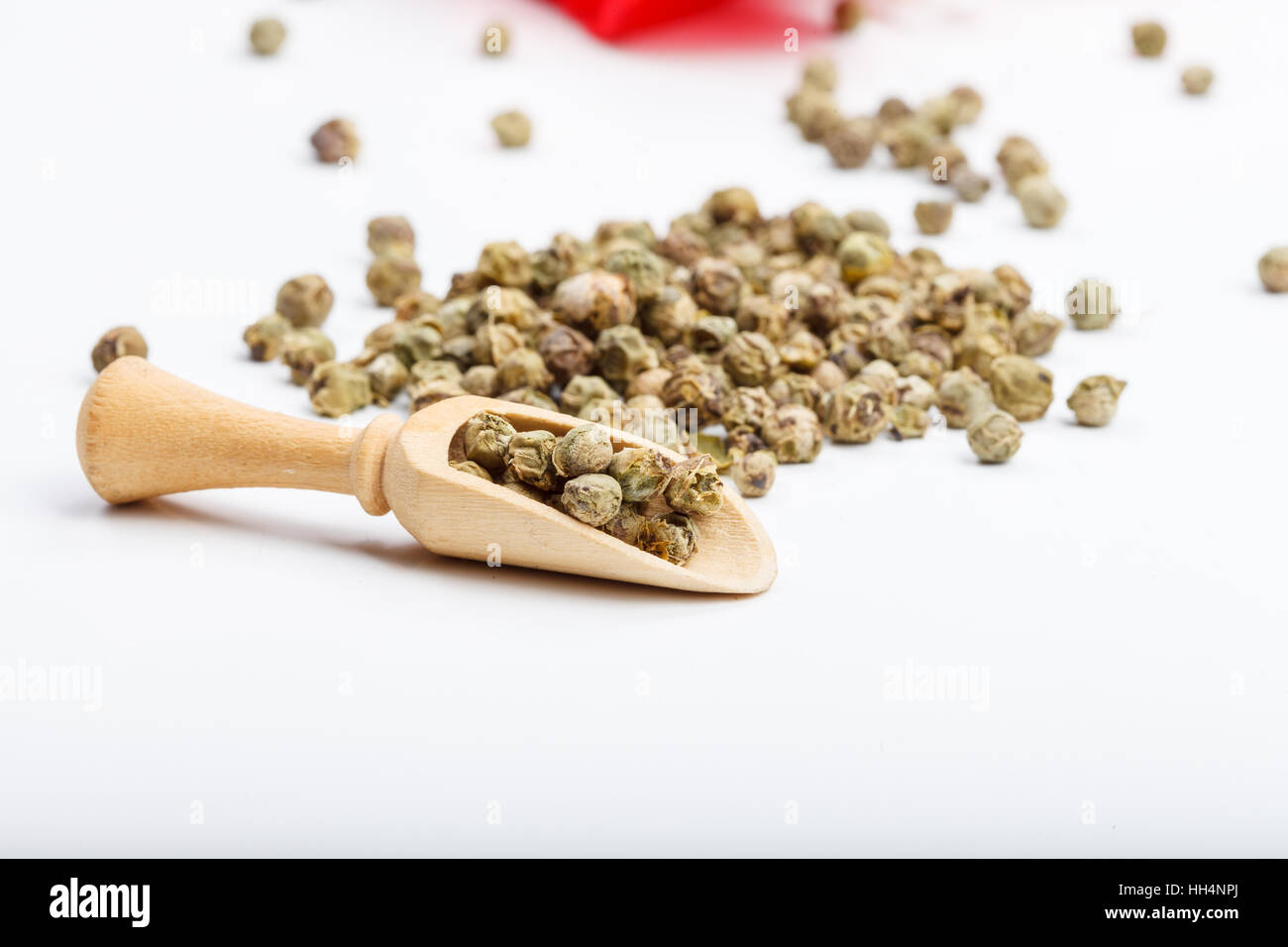 Green peppercorn seeds on white table with wooden handmade rustic scoop and a red fabric - Stock Image
