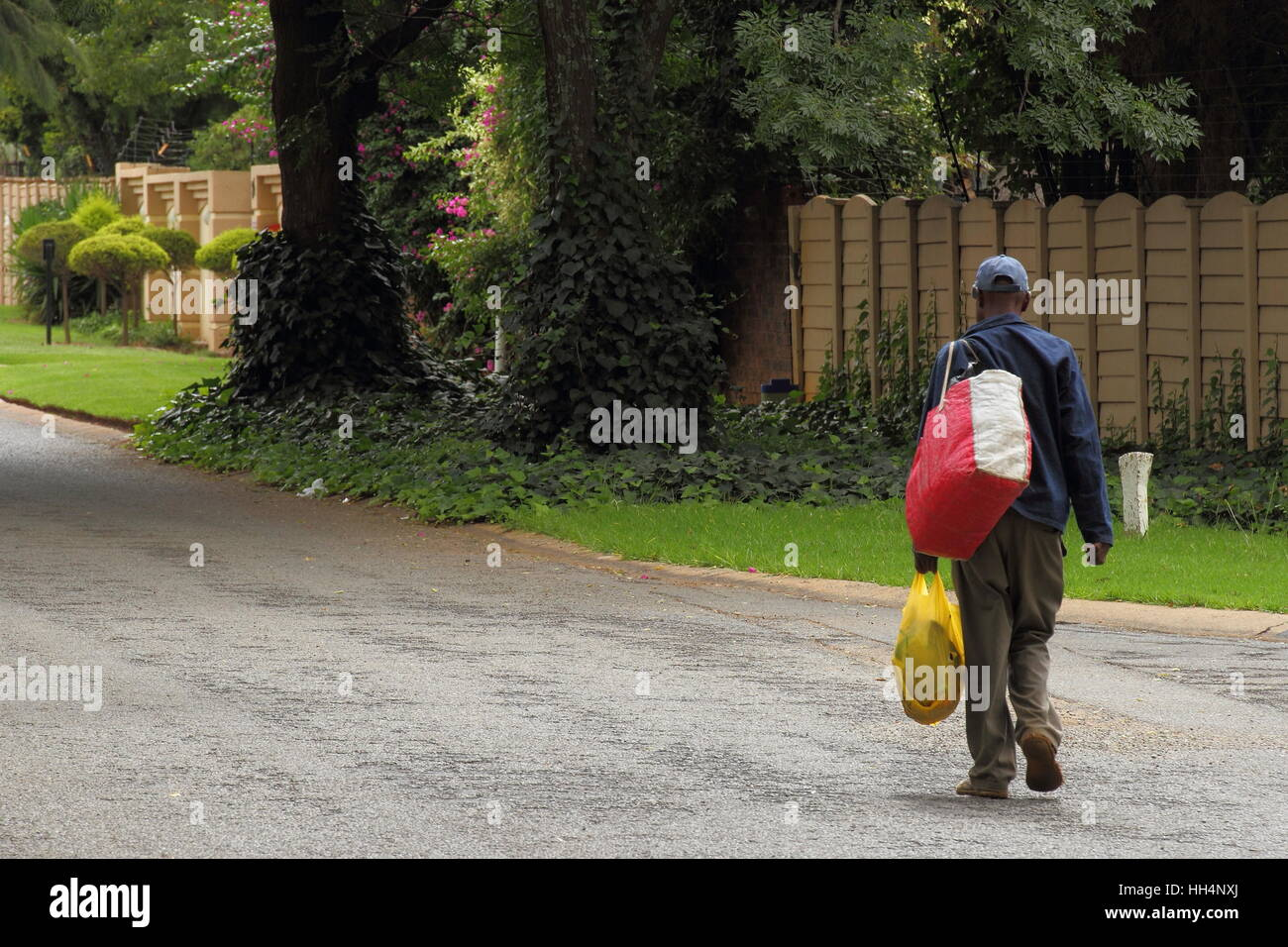 Homeless jobless man South Africa walks down a public street carrying his belongings image with copy space in landscape - Stock Image