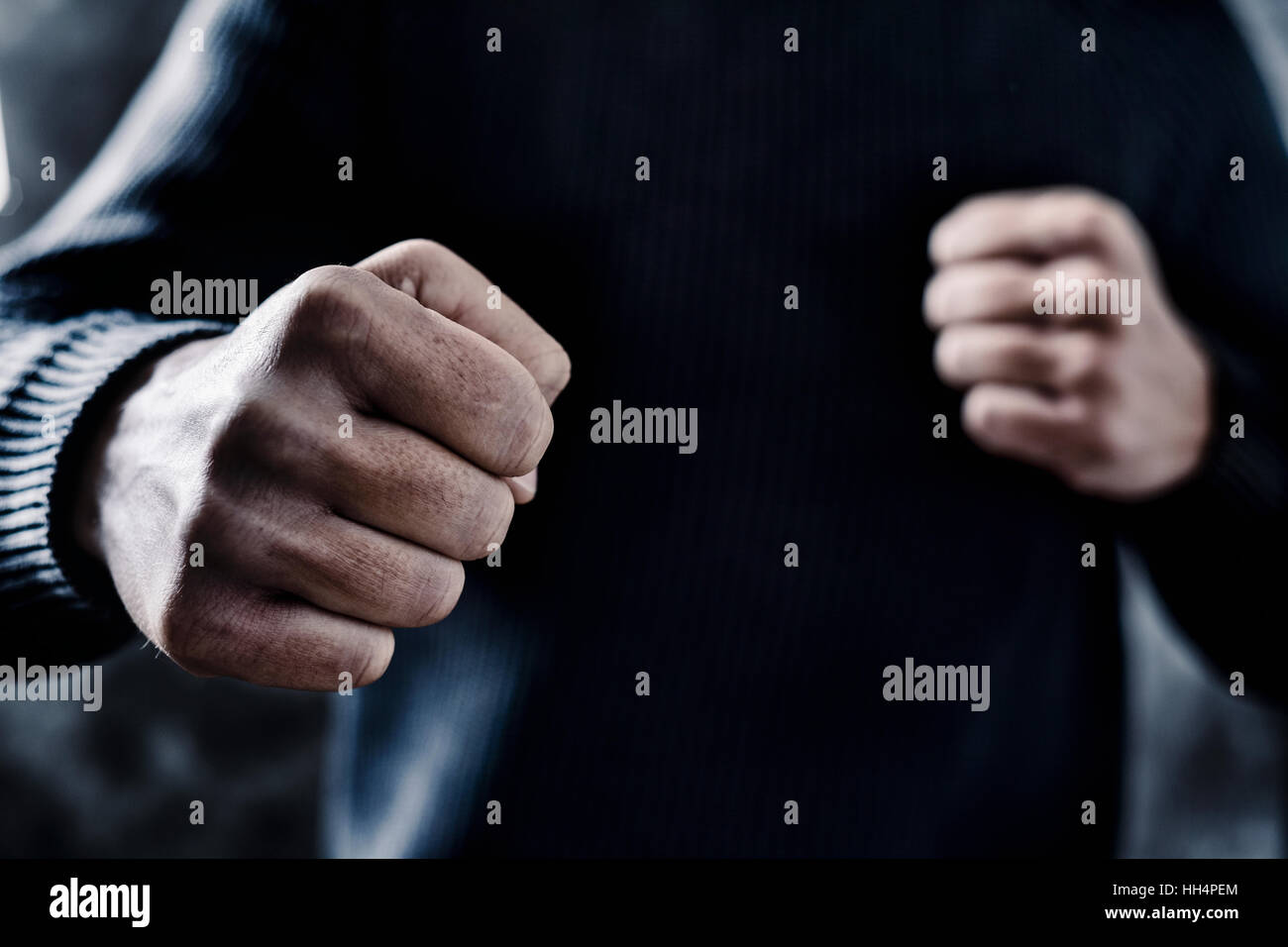 closeup of a young caucasian man in casual wear with a threatening gesture, ready to punch or fight with his fists - Stock Image