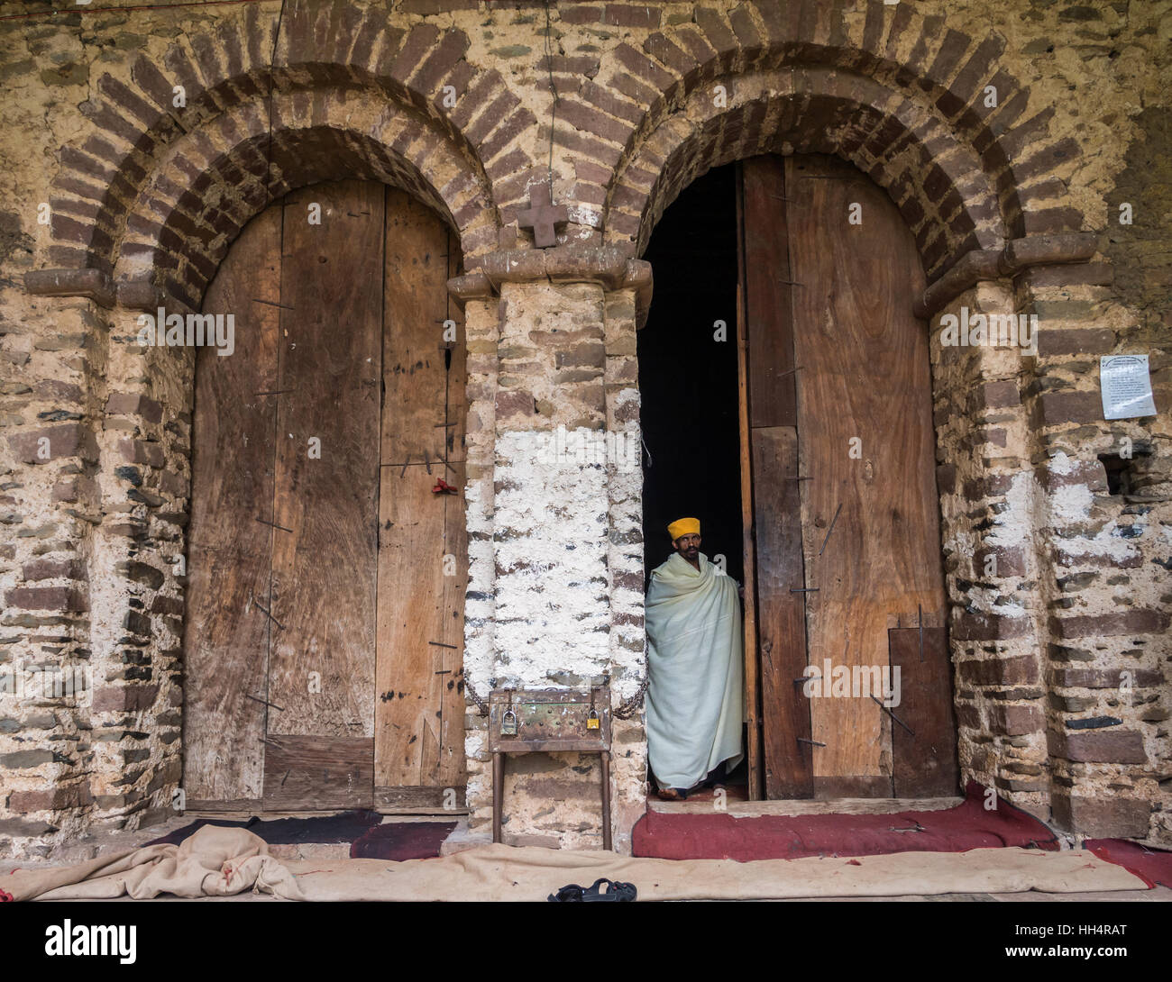 Ethiopian priest coming out of Yohannis Debre Birhan Selassie (Trinity and Mountain of Light) Church in Gondar - Stock Image