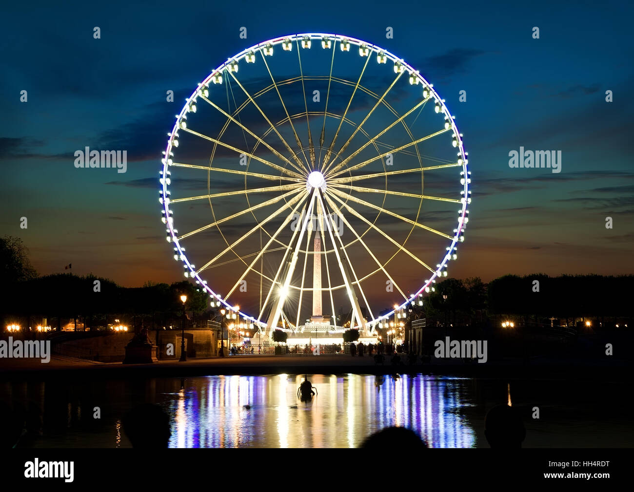 Illuminated ferris wheel and river Seine in Paris at sunset, France - Stock Image