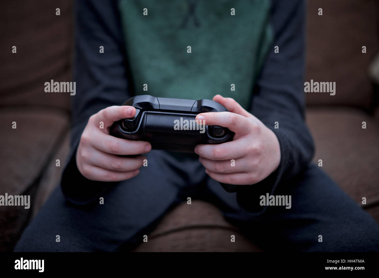 Close-up of a young boy holding video game controller. - Stock Image
