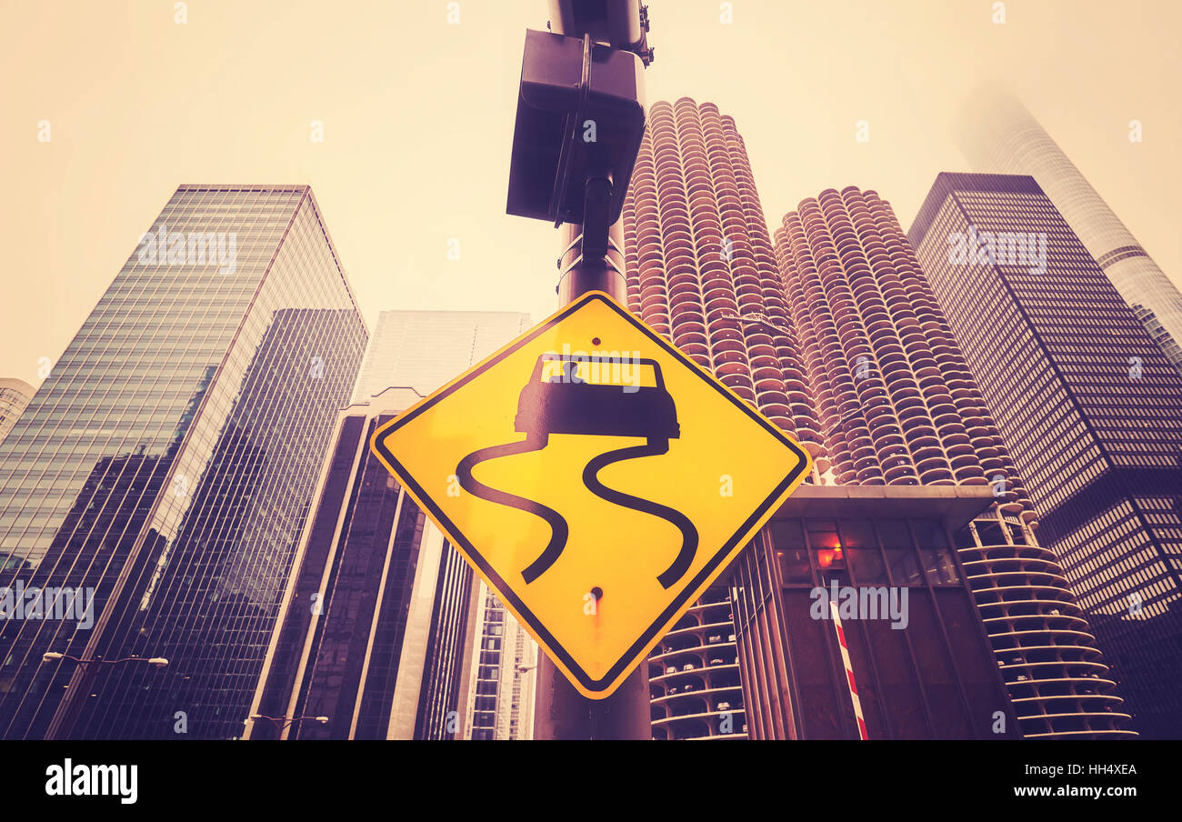 Color toned slippery when wet road sign with curvy tracks, Chicago skyscrapers in distance, conceptual picture. - Stock Image