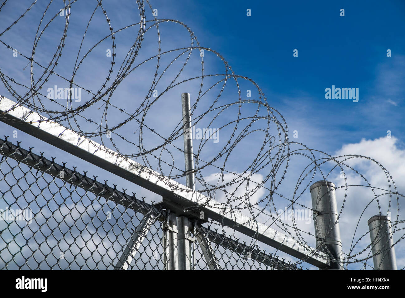 Razor sharp barbed wire tops a chained linked fence in a prison yard ...