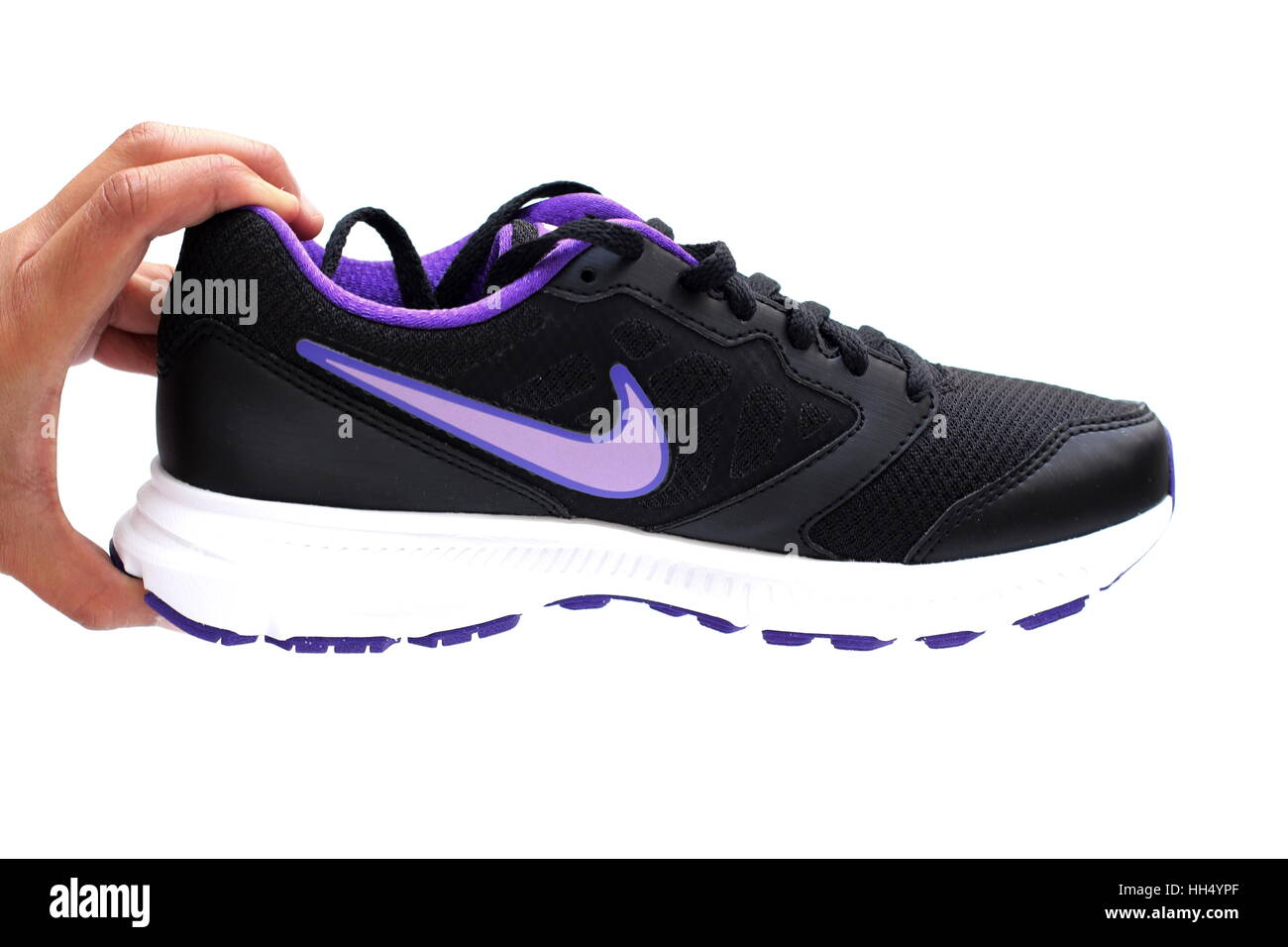 24497a45bc17 Close up of hand holding Nike shoes isolated against white background