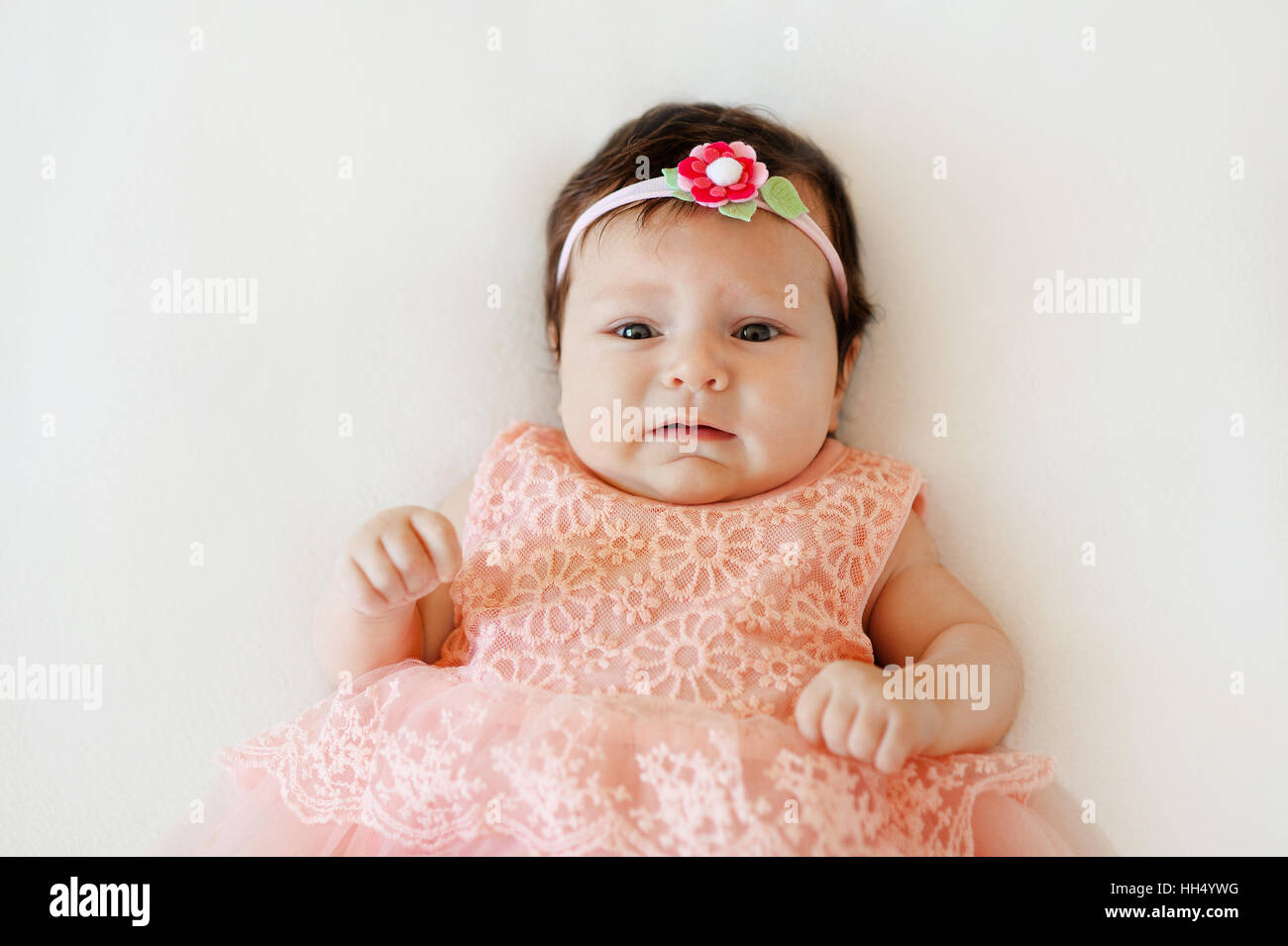 cute baby girl with sad face lies on a white blanket stock photo
