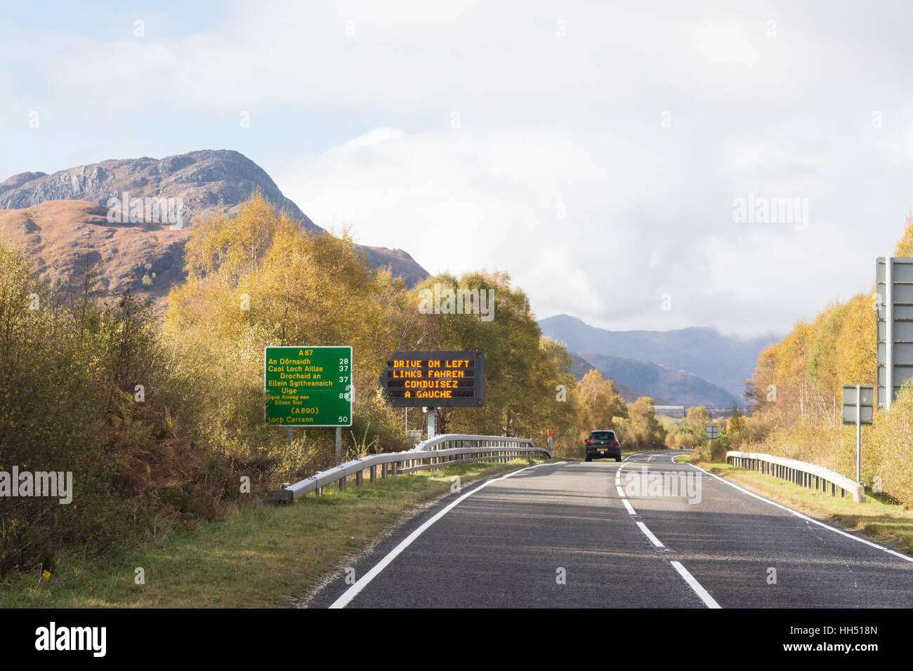 Drive on the left road sign and Gaelic road sign on the A87 in the Scottish Highlands, Scotland, UK - Stock Image