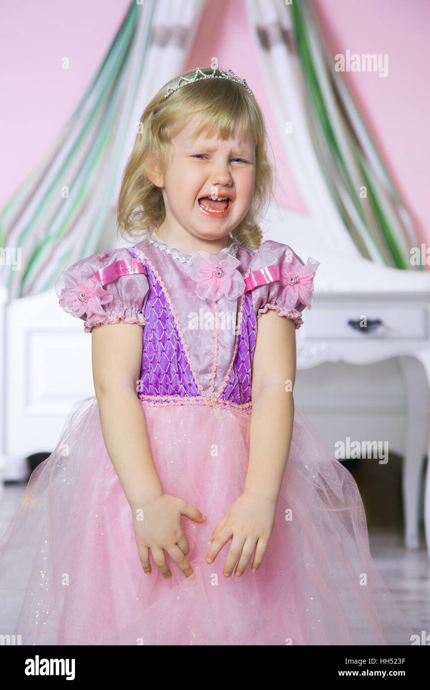 7a2dc0dc203e Little unhappy princess girl in pink dress and crown in her royal room is  crying.