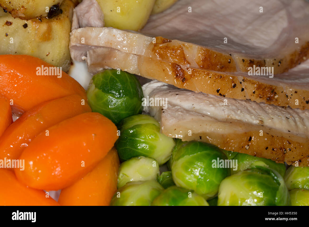 Cooked roast Pork joint with vegetables and potatoes, Stock Photo
