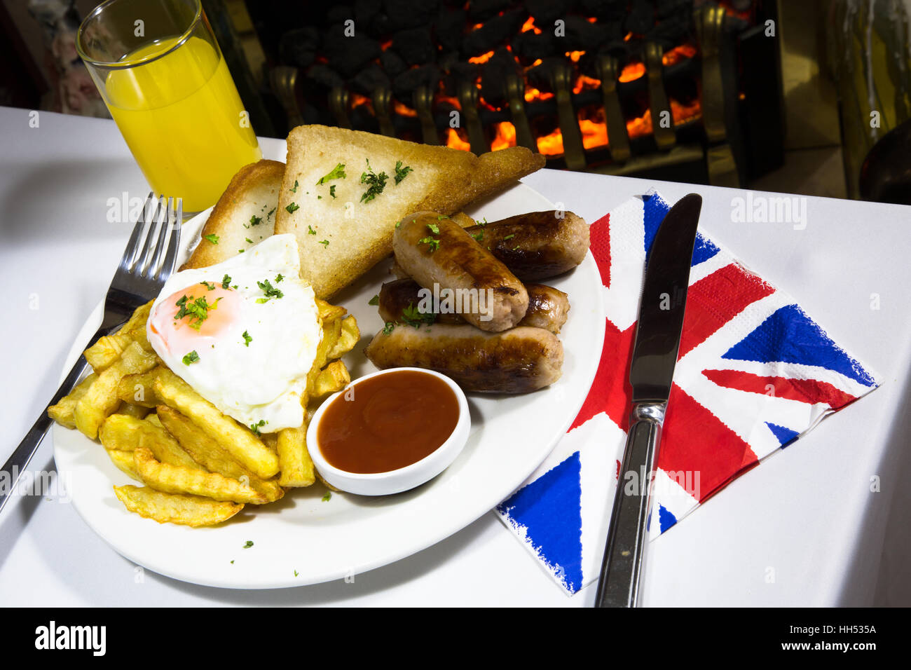 English pub dinner of Sausage, fried egg and chips/fries. - Stock Image