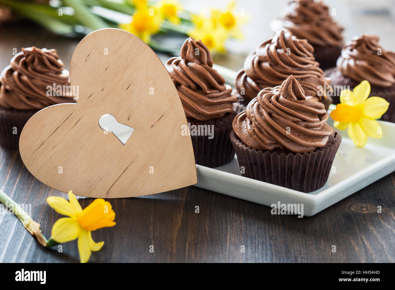 Delicious Mothers day  chocolate cupcakes  with spring flowers and wooden heart shape with free text space - Stock Image