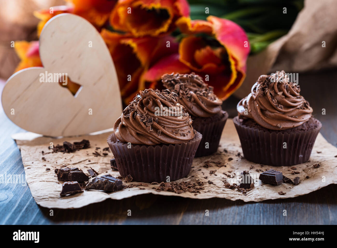 Delicious Mothers day  chocolate cupcakes  with spring tulips and wooden heart shape - Stock Image