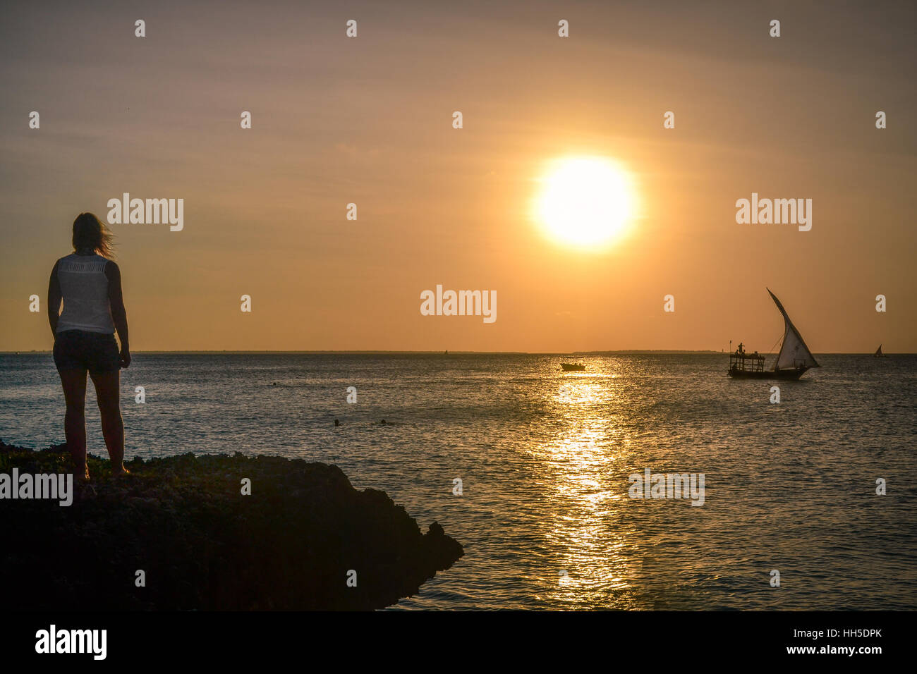 Amazing sunset with woman and boat - Stock Image