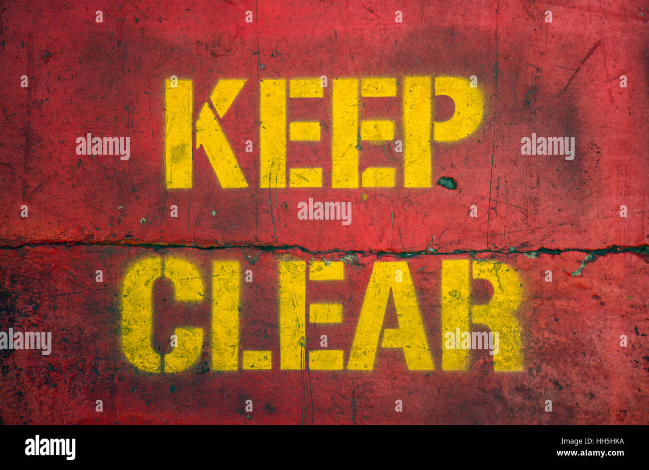 Worn and grungy Keep Clear sign stenciled on concrete. - Stock Image