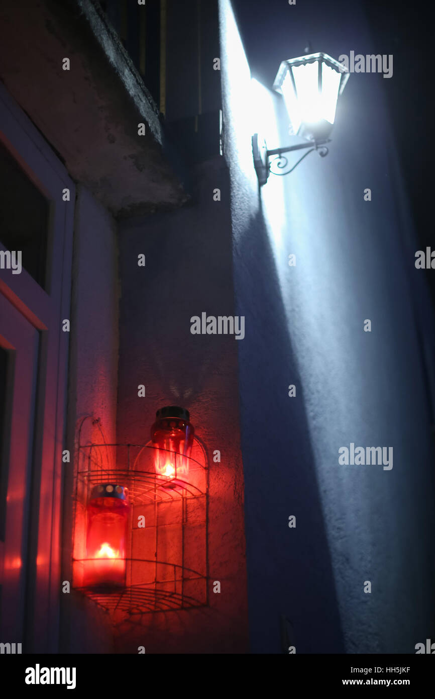 Burning lampions hanging on the house wall under the illuminating lamp. - Stock Image