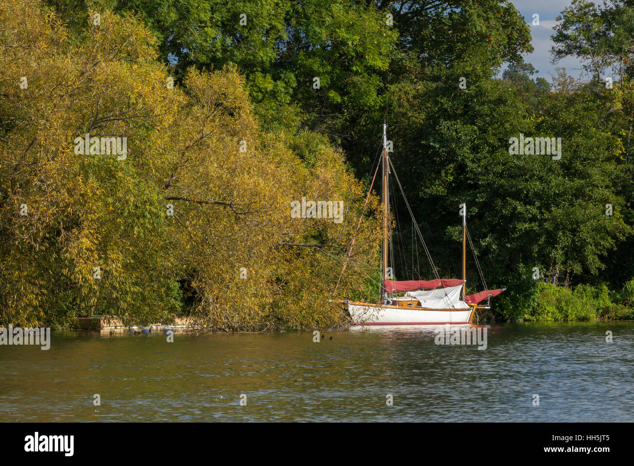 A sailboat moored on the River Thames near Hambleden Lock, in early autumn, Chilterns, Buckinghamshire, England - Stock Image