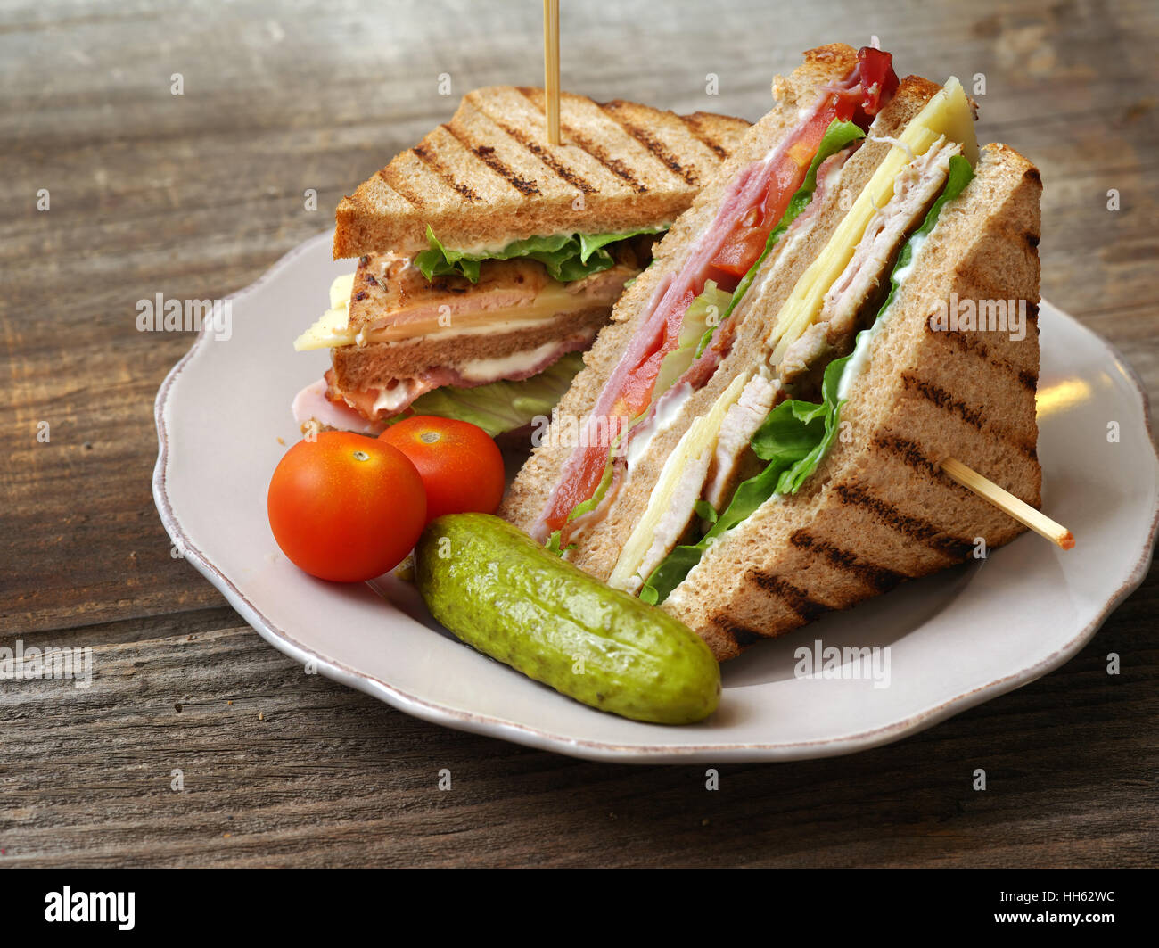Photo of a club sandwich made with turkey, bacon, ham, tomato, cheese, lettuce, and garnished with a pickle and - Stock Image