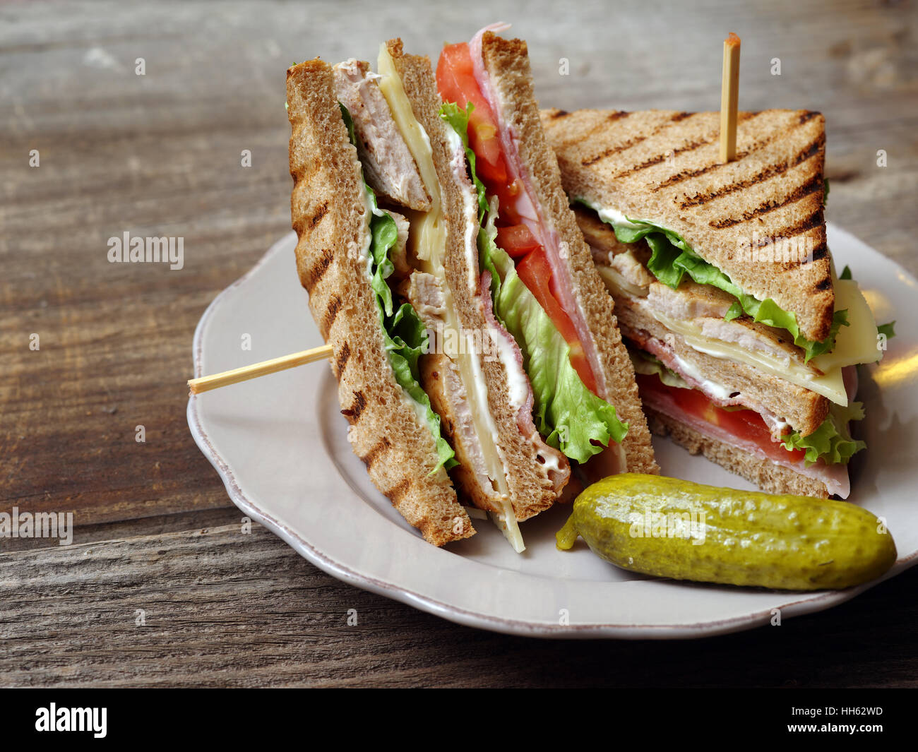 Photo of a club sandwich made with turkey, bacon, ham, tomato, cheese, lettuce, and garnished with a pickle. - Stock Image