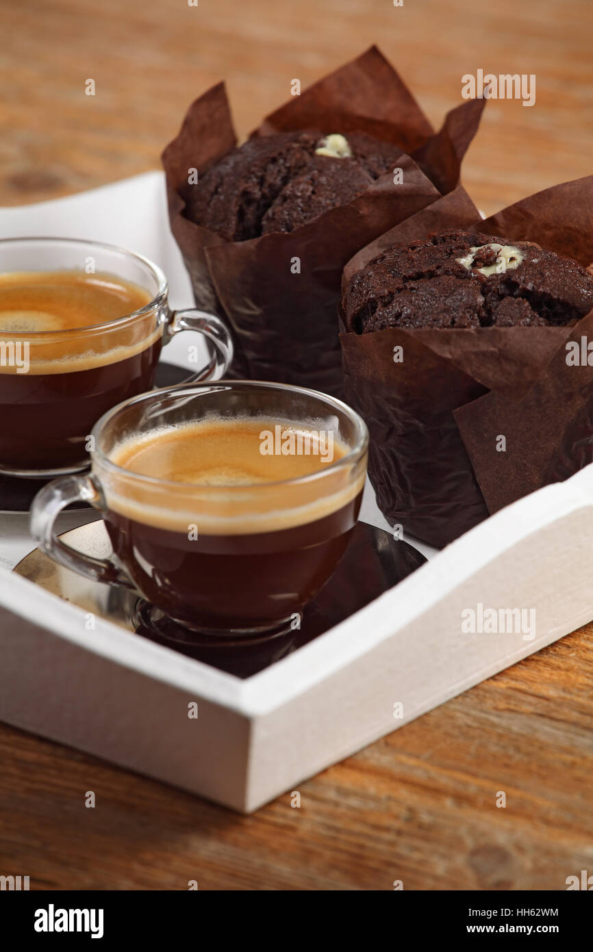 Photo of two moist chocolate muffins and two cups of espresso or coffee resting on a white serving tray. Shallow Stock Photo