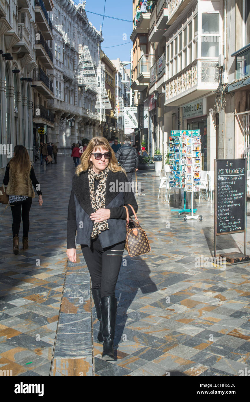 Blonde haired female shopper walks along the Calla Mayor in Cartagena, Murcia, Spain - Stock Image