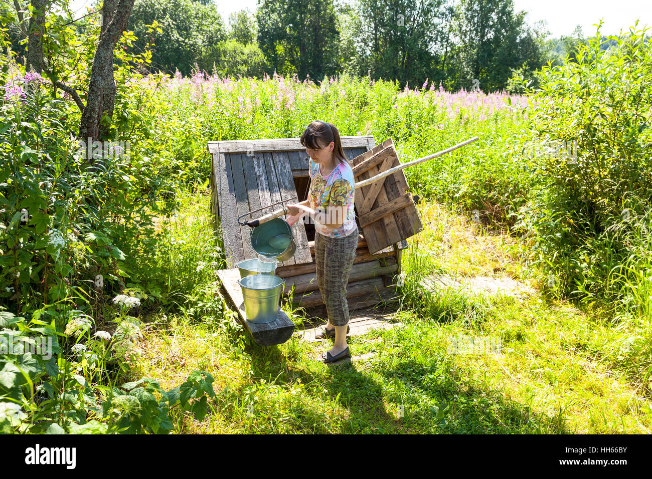Young attractive woman near the village wooden water well in summer sunny day Stock Photo