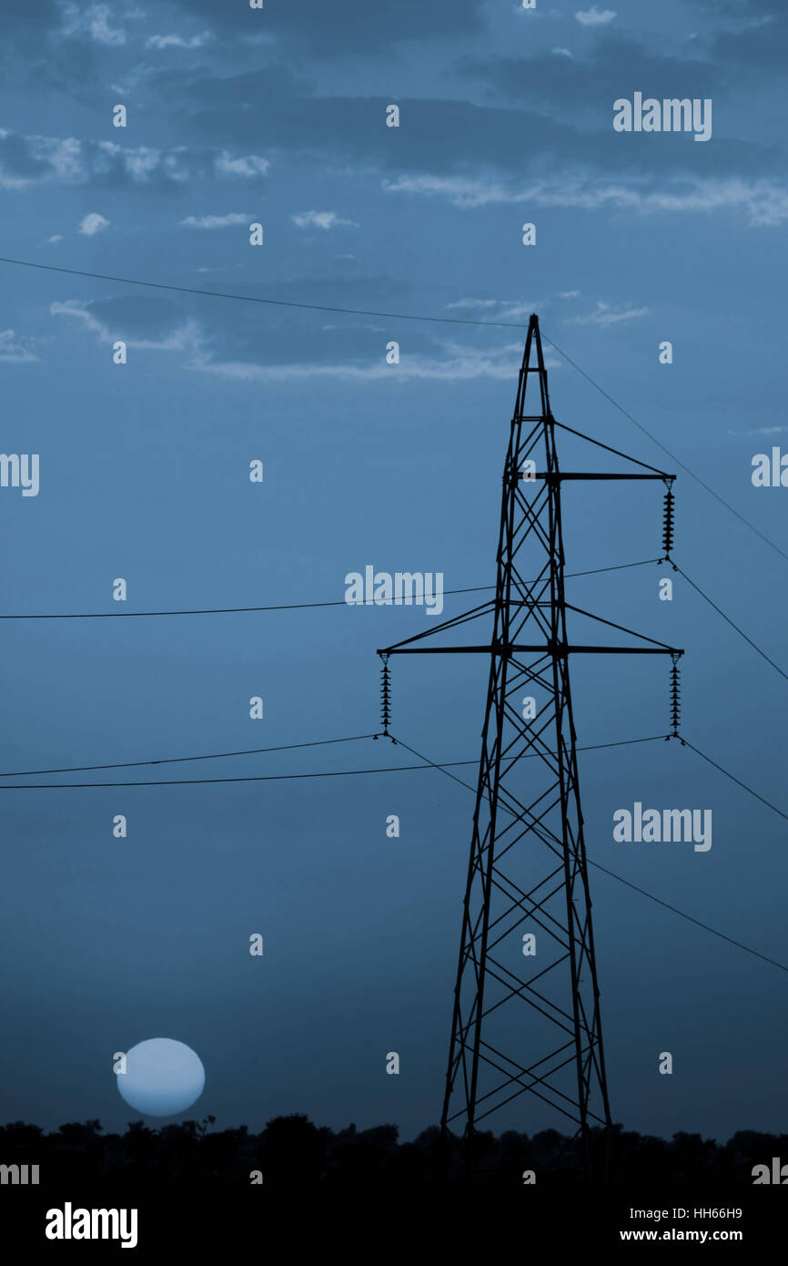 Electricity pylon at sunset in India, Rajasthan province. - Stock Image
