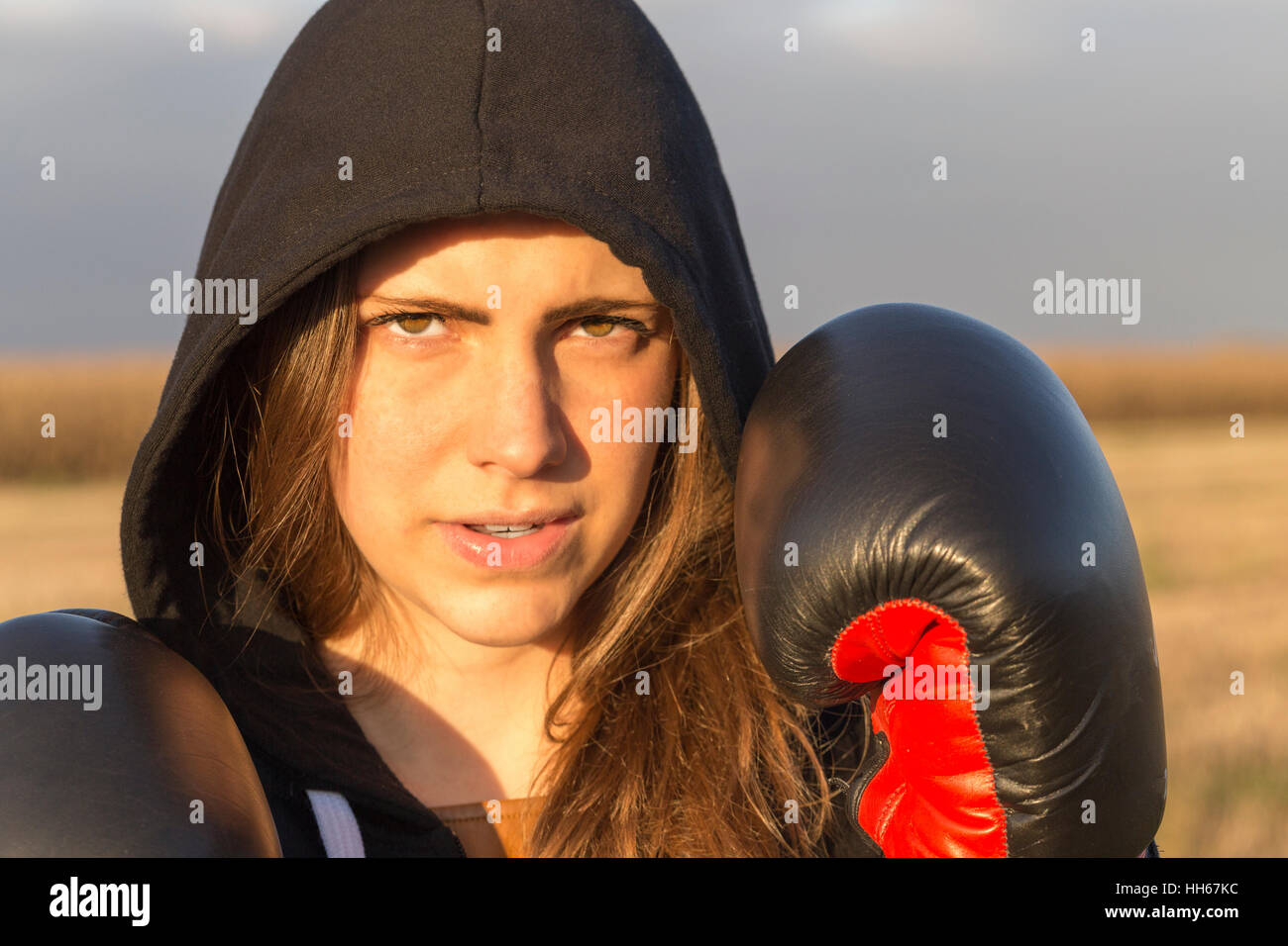 A young brunettes girl with boxing gloves - Stock Image