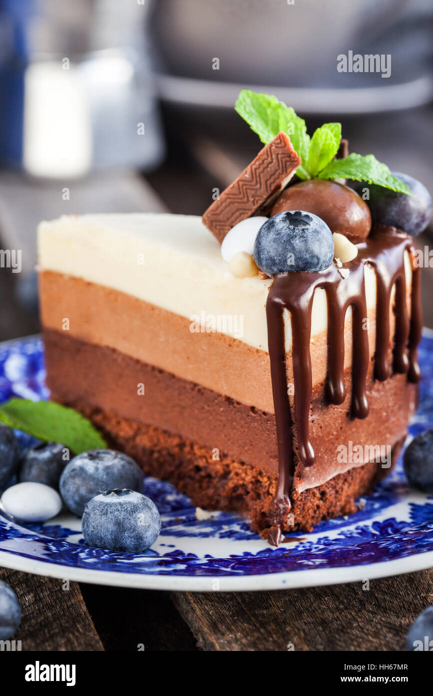 Piece of delicious three chocolate mousse cake decorated with fresh blueberry, mint and candies - Stock Image